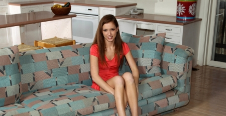 Maddy O'Reilley - sitting on couch, red head, sideboard, salmon pink mini dress, phone, bowl