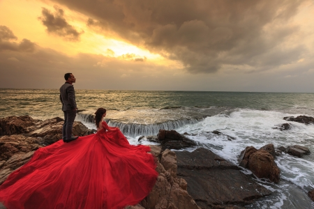 Red gown _watching the sunset - couple, sea, pretty, red, rocks, female, male, models, dress, man, sunset, woman, photography, people