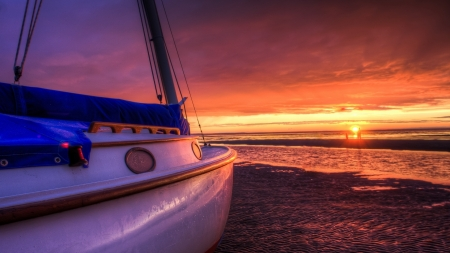 Boat shored at a low-tide beach at sunset - sunset, sail, sea, beach, gold, water, tide, boat, ship, golden hour, coast, shore, sun, sailing, clouds, old, sand, ocean, golden, sky