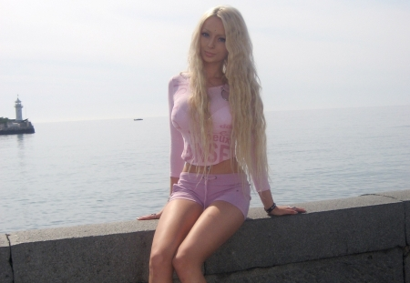 Valeria Lukyanova - barbie doll look a like, stone wall, headland, cream top, seaside, platinum blonde, sitting, violet coloured pants, lighthouse