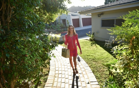 Emma Hix - garages, zip up front, house, grass, pendant, blonde, trees, handbag, brick path, motion light, white rocking chair, roman style ankle bracelets, walking, flat shoes, pink dress