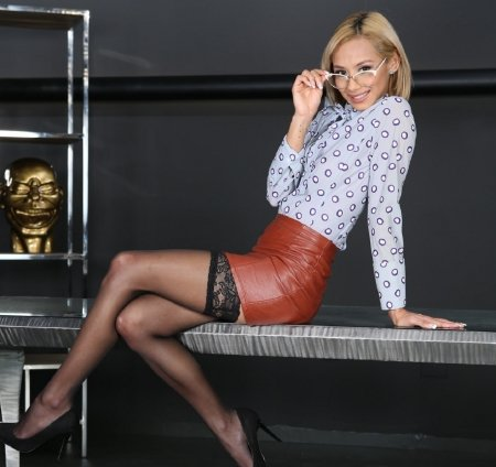 Veronica Leal - orange leather mini skirt, earrings, blonde, sitting, black thigh high stockings, glasses, long sleeves, blue circle pattern, white blouse, black heels