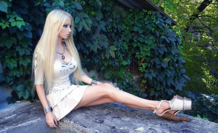 Valeria Lukyanova Barbie Doll look - heavy eye make up, greenery, white dress with pleats, sitting on stone steps, platinum blonde, heels, jewelry