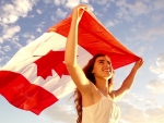 Pretty Woman Holding Canadian Flag in the Clouds