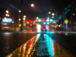 A downtown road covered in rain, glowing from nearby traffic lights