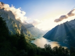 A lake in a mountainous valley under a sunlit sky