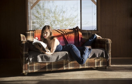 Riley Reid - blue knit top, brunette, plaid design, large window, posing on couch, denim jeans, throw rugn couch, wood panelled walls, arm bracelets