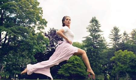 Aly Raisman - leaping, brunette, white top, violet skirt, trees