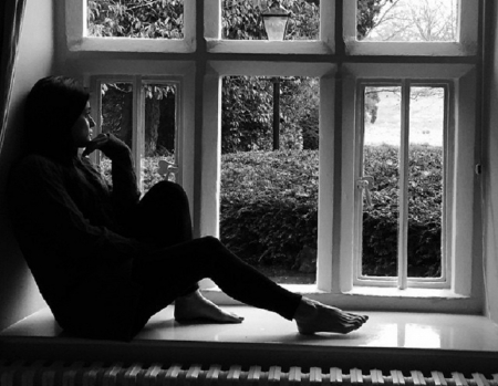 Christina Salti - Brunette, sweater, siting on window sill, Black and white image, bare feet, looking out of window