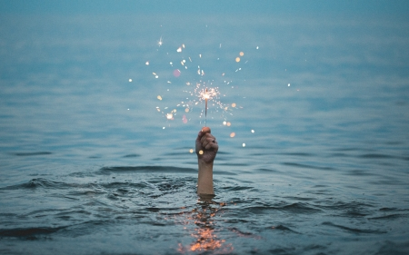 Person holding up a sparkler while underwater - water, people, fireworks, sparkler, blue, lake, underwater, firework, glow, sparkle