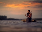 Girl with violin at sunset