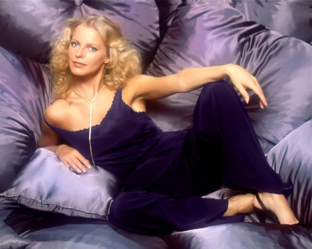 Cheryl Ladd - blue eyes, sleeveless suit, pendant, black heels, blonde, posinh on couch, dark blue trouser suit