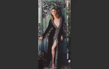 Angela Lindvall - plunging neck line, long black dress, bare feet, open front slit, red hair, standing in doorway, flowering vines