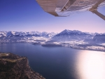 View from an airplane over a mountainside lake