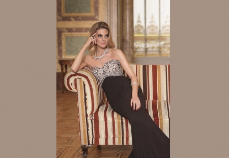 Amaia Salamanca - marble floors, jewelry, window, columns, black, sequin top, brunette, walls, sitting on couch, matching necklace and bracelet, strapless dress, ring