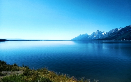 Side view of the Grand Tetons from across Jackson Lake in Wyoming - water, grass, sky, mountains, usa