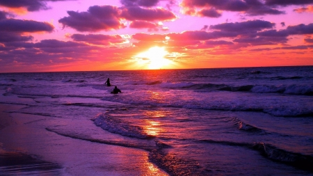 A couple swimming at an ocean beach during a purple sunset - ocean, sunset, sky, coast, glow, sun, foam, clouds, beach, water, purple, golden hour