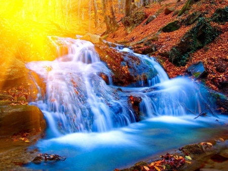 A beautiful waterfall - blue, rural, glow, sun, brown, yellow, sunny, photography, water, waterfall, nature, forests, sunshine