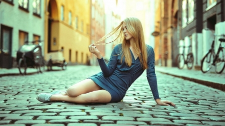 BLONDE IN BLUE SHORT DRESS - sitting on strret, playing with her hair, blue dress, buildings, blonde, cobblestone, bicycles