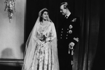 HRH The Princess Elizabeth with HRH The Prince Phillip on their wedding day - wedding dress, curtains, Lieutenant rank, flower bouquet, cutlass, RN uniform, sconce on wall, jewelry