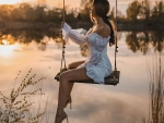 Brunette straddling the swing at sunrise