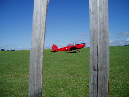 Between the fence. - fence, red, plane, grass, sky