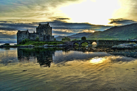 Eileen Doonan Castle - mountain, refelection, walls, towers, sunlight, yellow, waves, castle
