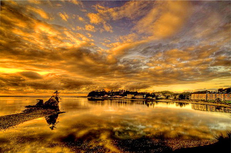 Evening gold - shore, water, rock, golden clouds, reflections city, sky