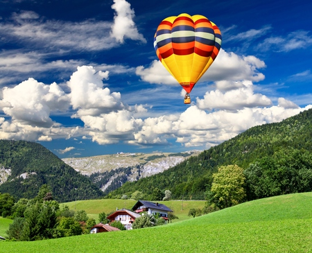 Landscape - colorful, hills, grass, peaceful, landscape, hot air balloons, blue, sky, colors, splendor, balloon, mountains, nature, hot air balloon, trees, houses, beauty, beautiful, lovely, balloons, clouds, pretty, house, green, view