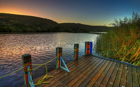 Sunset - colorful, reeds, beautiful, sunset, clouds, dock, splendor, beauty, river, reflection, hills, lovely, view, pier, colors, sky, trees, lake, water, peaceful, nature, landscape