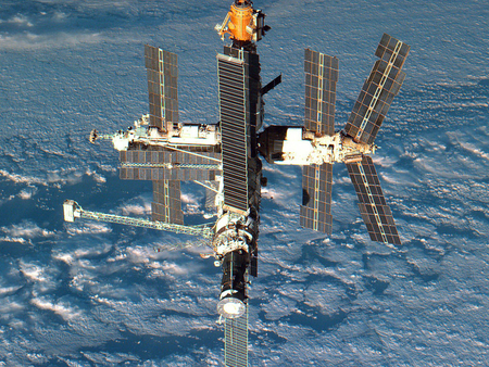 international space station - solar panels, clouds, planet, shadow